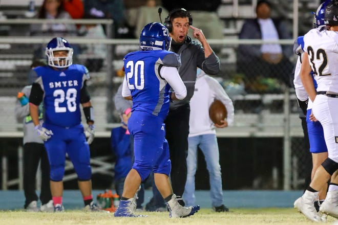 Smyer coach Scott Funke instructs Gilbert Gil (20) during a District 2-2A Division II game on Friday, Oct. 30, 2020, against Sudan at Bobcat Stadium in Smyer.