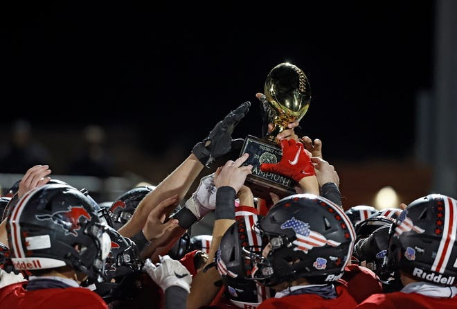 Shallowater players lift up the District 1-3A Division I championship trophy after the Mustangs defeated Slaton 42-6 on Friday, Oct. 30, 2020, at Todd Field in Shallowater.