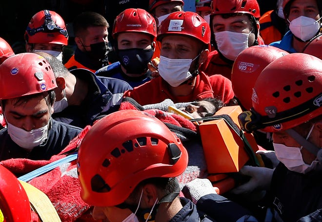Medics and rescue personnel carry an injured person from the debris of a collapsed building in Izmir, Turkey, on Saturday. Rescue teams on Saturday plowed through concrete blocks and debris of eight collapsed buildings in Turkey's third largest city in search of survivors of a powerful earthquake that struck Turkey's Aegean coast and north of the Greek island of Samos, killing dozens of people. Hundreds of others were injured.