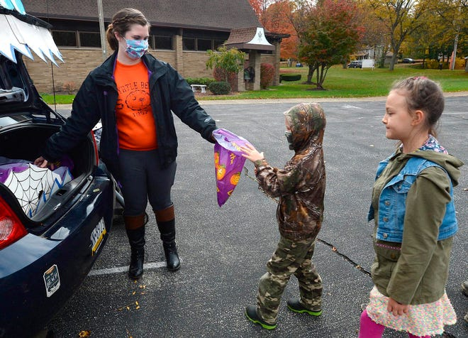 Samantha Ruiz-Bueno, left, passes out candy to Boaz Pettis, 6, of Millcreek Township, Pa., and his sister Callista Pettis, 8, during the Drive-thru Trunk or Treat event for kids at the Fairview United Methodist Church on Saturday in Fairview, Pa.