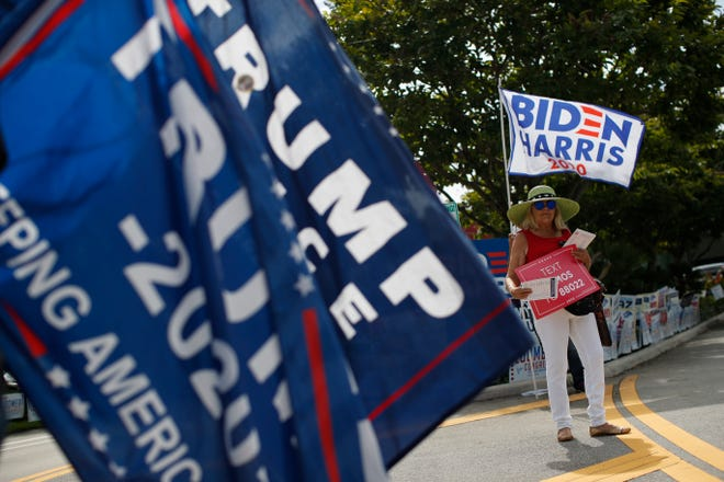 Supporters of President Donald Trump and former Vice President Joe Biden wave flags and hand out information to arriving voters outside an early voting polling station in West Palm Beach on Friday.