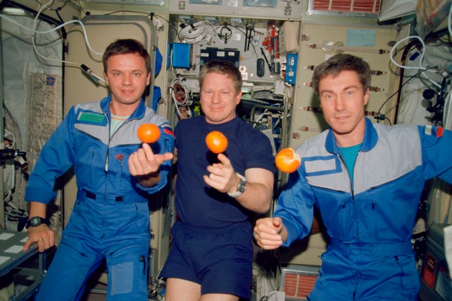 the Expedition 1 crew members pose with fresh oranges onboard the Zvezda Service Module of the Earth-orbiting International Space Station on Dec. 4, 2000. Pictured, from left, are cosmonaut Yuri P. Gidzenko, Soyuz commander; astronaut Bill Shepherd, mission commander; and cosmonaut Sergei K. Krikalev, flight engineer.