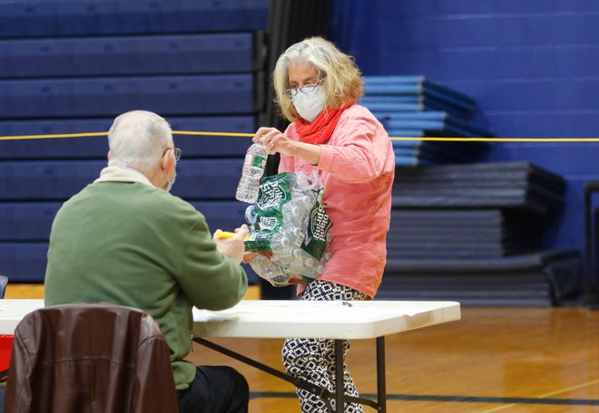 York Town Clerk Mary-Anne Szeniawski hands out water as volunteers process absentee ballots at the York High School gymnasium Saturday, Oct. 31, 2020.
