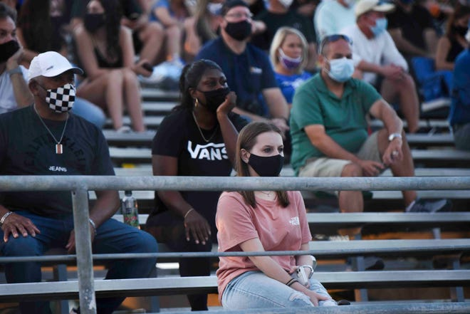 Fans are seen wearing masks during a high school football game at Wellington High School earlier this season. The Seminole Ridge-Santaluces game scheduled for Wellington High on Saturday afternoon was cancelled due to COVID-19, the district announced late Friday.