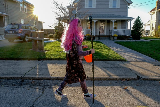 Lillian Souza, 9, leads the way for her mom and sister while trick-or-treating in East Providence on Saturday.