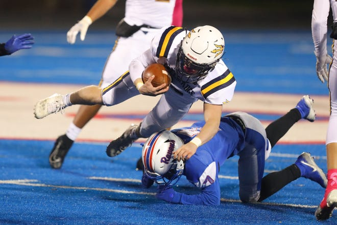 Tallmadge junior Cole Thomas leaps for extra yardage on a play during Friday night's game against Ravenna High School.