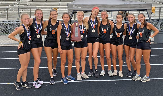 The Sarasota High girls cross country team pose with their trophy after winning the Class 4A-District 13 title Saturday morning at North Port High.
