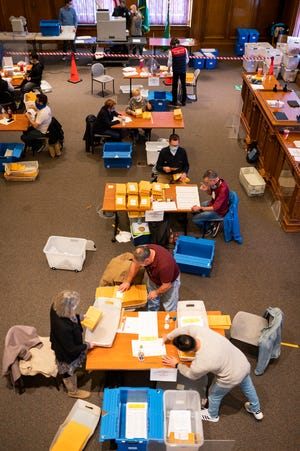Volunteers and city employees count ballots in Worcester City Hall.