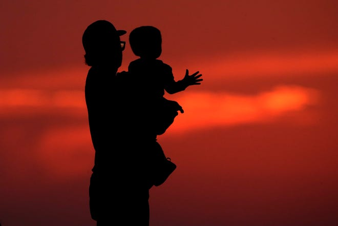 This photo from June 26 shows a silhouette against the sky of a man holding a child, as they watch the sunset from a park in Kansas City, Mo.