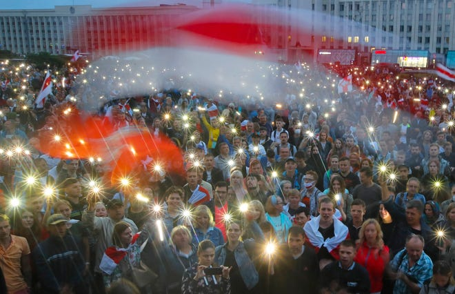 In this Aug. 19 file photo, Belarusian opposition supporters light phones lights and wave an old Belarusian national flags during a protest rally in front of the government building at Independent Square in Minsk, Belarus.