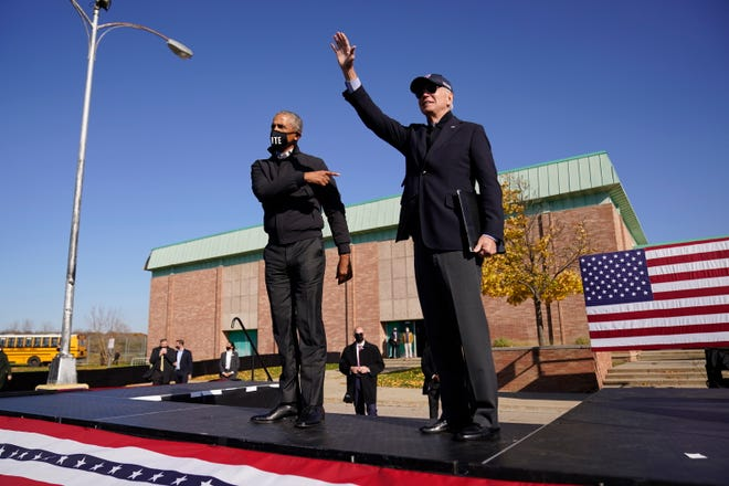 Democratic presidential candidate former Vice President Joe Biden, right, and former President Barack Obama greet each other at a rally Saturday in Flint, Mich.
