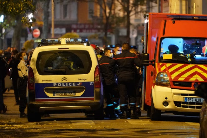 Police officers and rescue workers block the access to the scene after a Greek Orthodox priest was shot Saturday while he was closing his church in Lyon, France.