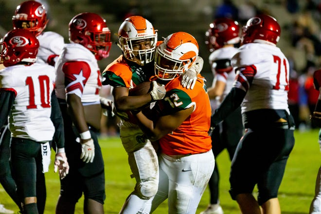 Eastside running back Keonte Macon celebrates with teammate Leonard Walker (72) against Santa Fe at Citizens Field in Gainesville.