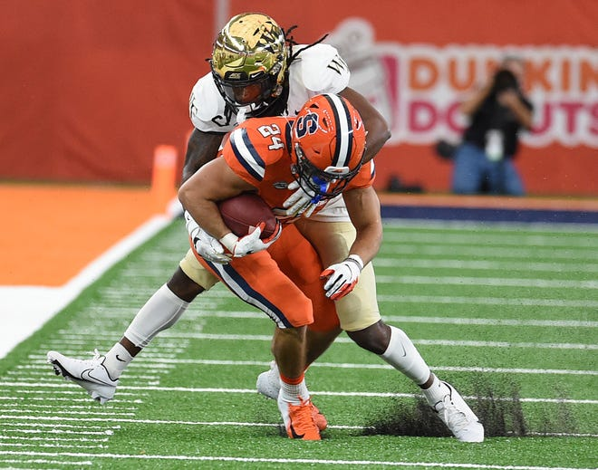Wake Forest defensive back Ja'Sir Taylor, rear, tackles Syracuse running back Cooper Lutz on Saturday afternoon.
