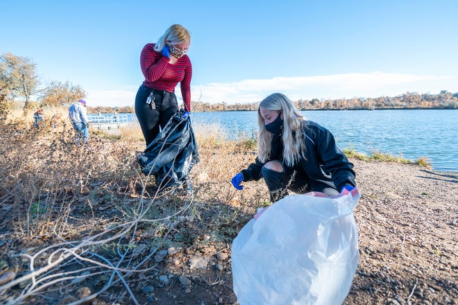 Colorado State University Pueblo students Rebecca Parker, left, and Emma Sommer pick up trash along the north shore of Runyon Lake.