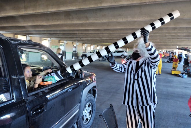 """As Beetlejuice, Pueblo Police Department volunteer Mike Massey dispenses treats from the """"Sandworm"""" during Saturday's """"trunk or treat."""""""