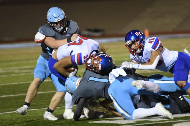 Pueblo West High School senior defensive end Lukas Moran (back left) and his teammates tackle a Fountain Fort-Carson receiver during the Cyclones' 35-21 loss to the Trojans at Cyclones Stadium Friday.