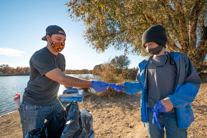 Colorado State University Pueblo student Kyle O'Rourke, left, hands a pair of gloves to Chase Bailey, 10, as they take part in a community cleanup Friday at Runyon Lake.