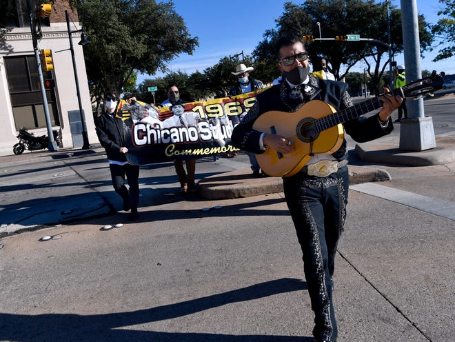 José Chavez crosses North First Street leading a group of about 30 in song as they commemorate the 1969 Chicano student walkout in downtown Abilene on Saturday morning. The group marched from the Abilene Independent School District headquarters to Everman Park. This event recreated a similar march last year on the 50th anniversary of the protest.