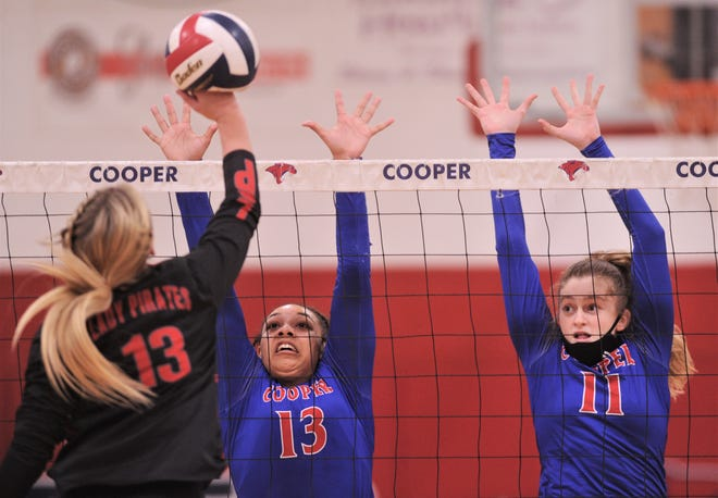Abilene Cooper's Jennika Willis (13) and Ana Tetja (11) defend at the net as a Lubbock-Cooper player hits the ball. Lubbock-Cooper beat the Lady Coogs 3-1 in the District 4-5A match Friday at Cougar Gym.