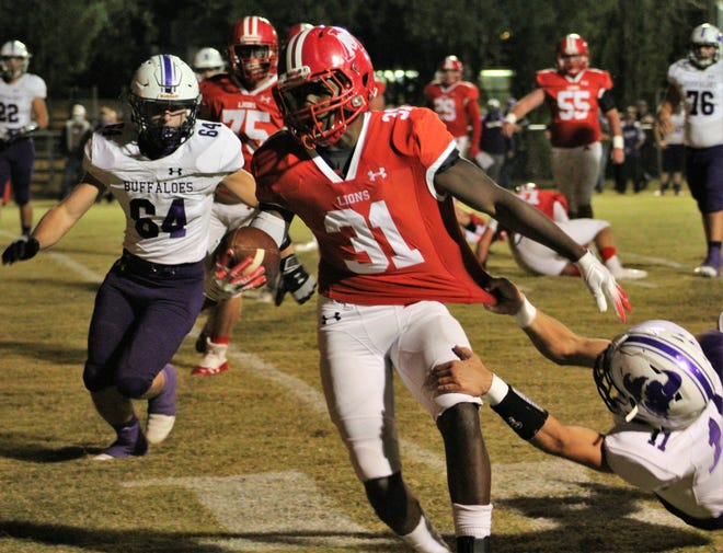 Albany running back Jaheim Newton (31) is slowed by the grasp of Cross Plains defender Ketch Thomas (11) during the first half of their game Friday in Albany. The Lions won, 35-0. Oct. 30 2020