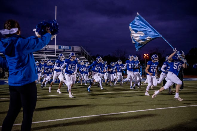 Harper Creek varsity football players enter the field before taking on Parma Western on Friday, Oct. 30, 2020 at Harper Creek High School. Harper Creek defeated Parma Western 30-13.