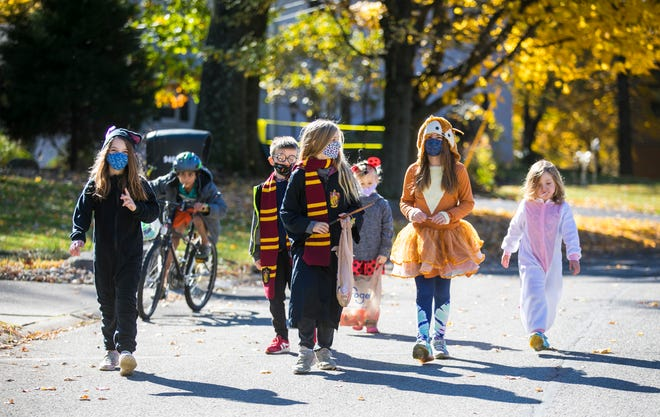 Three families, who said they couldn't go out to trick or treat tonight for Halloween, took to the streets in their neighborhood early, Saturday, Oct. 31, 2020. But the looks of their bags, going out early was not an issue. (L-R): Emily Horn, 9, Adarsh Dinesh, 9, Elliot Avery, 7, Aviah Avery, 9, Hannah Avery, 4, Sarah Horn, 9 and Anna Horn, 5.