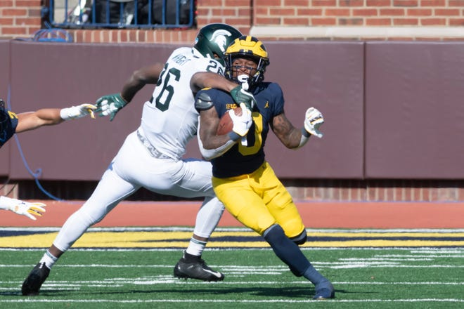 Michigan wide receiver Giles Jackson slips a tackle by Michigan State running back Brandon Wright in the second quarter.
