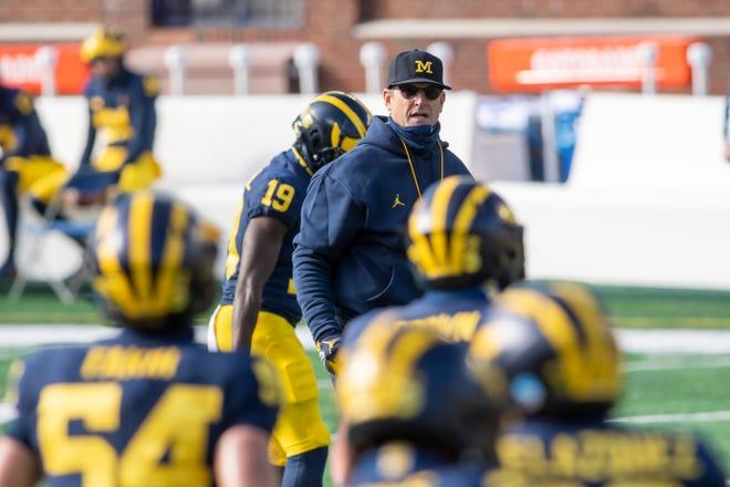 Michigan head coach Jim Harbaugh keeps an eye on his team during warmups.