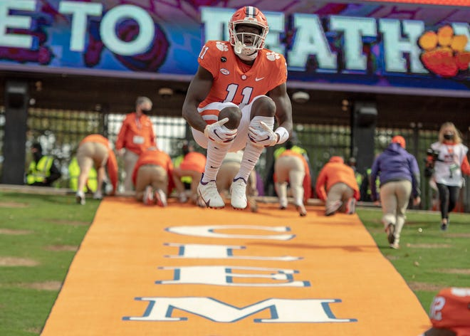 Clemson wide receiver Ajou Ajou(11) jumps as the last player running down the hill before the game against Boston College, Oct 31, 2020; Clemson, South Carolina, USA;  at Memorial Stadium. Mandatory Credit: Josh Morgan - USA TODAY Sports