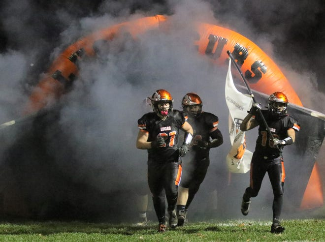 Members of the Lucas Cubs football team run onto the field ahead of their 2020 Regional Semifinal game against McDonald.
