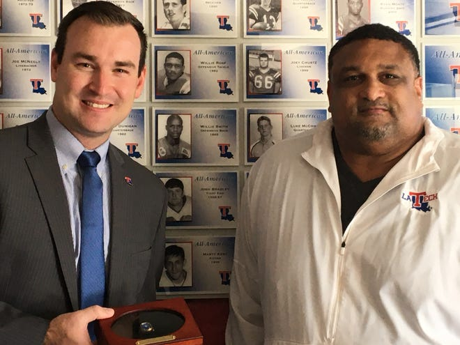 Louisiana Tech Hall of Fame football player Willie Roaf, right, presents Tech Senior Associate Athletic Director for External Operations Saturday, Oct. 31, 2020.
