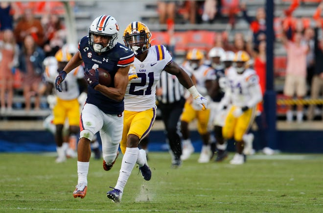 Oct 31, 2020; Auburn, Alabama, USA;  Auburn Tigers receiver Anthony Schwartz (1) scores a touchdown against LSU Tigers safety Jordan Toles (21) during the fourth quarter at Jordan-Hare Stadium. Mandatory Credit: John Reed-USA TODAY Sports
