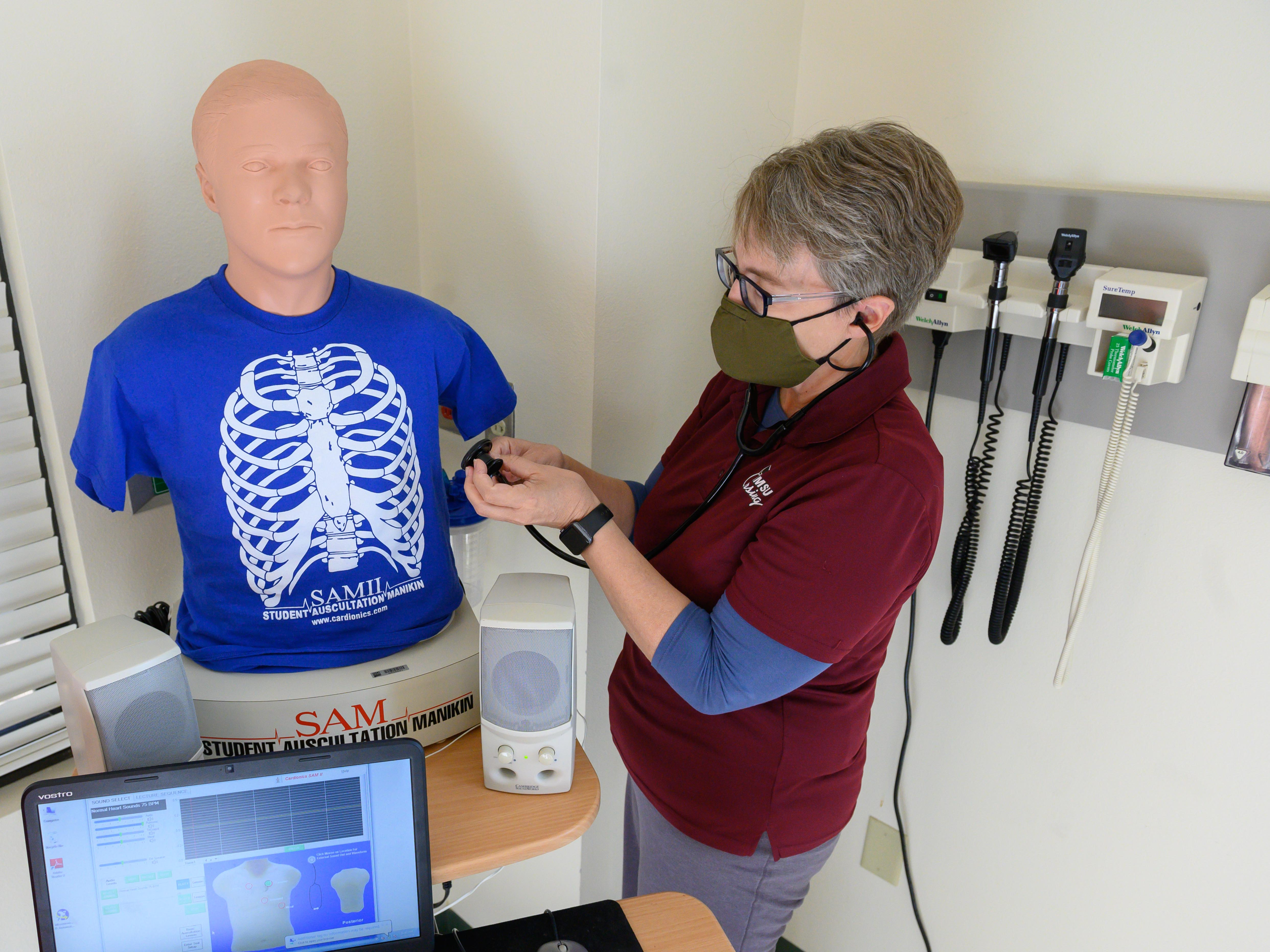 Alexa Doig, director of the School of Nursing at New Mexico State University, performs a physical assessment on a training mannequin inside of a lab at NMSU's College of Health and Social Services in October 2020.