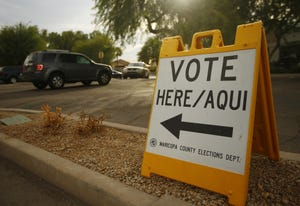A sign for voting directs traffic into a business parking lot on the last day of early voting in Chandler on Oct. 30, 2020.