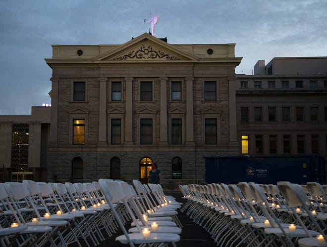 At the Day of the Dead COVID Memorial, 500 chairs, each with a tea candle on it, sit in front of the Rose Garden at the Arizona State Capitol On Oct. 30, 2020, to represent the nearly 6,000 Arizonans who have died due to COVID-19.