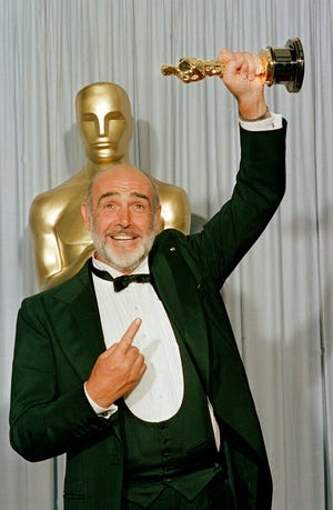 """FILE - In this file photo dated April 11, 1988, Sean Connery holds up his best supporting actor Oscar for """"The Untouchables"""" at the 60th annual Academy Awards in Los Angeles, Ca., USA.  Scottish actor Sean Connery, considered by many to have been the best James Bond, has died aged 90, according to an announcement from his family. (AP Photo/Lennox McLendon, FILE)"""