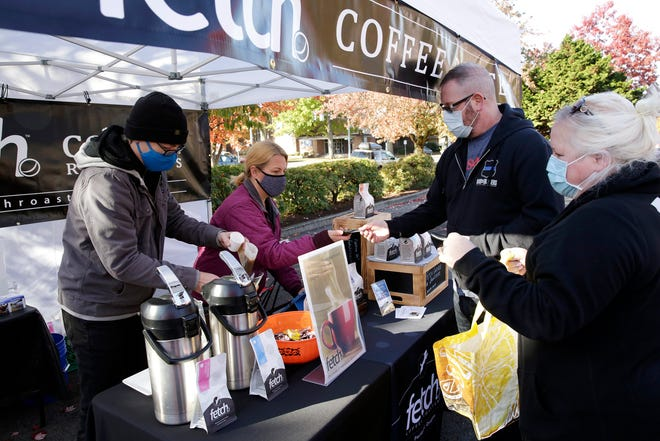 Todd Witter (left) and Sarah Witter of Fetch Coffee Roasters sell coffee to Drew Donoho and Kristina Donoho at the Salem Saturday Market in Salem, Oregon, on Saturday, Oct. 31, 2020.