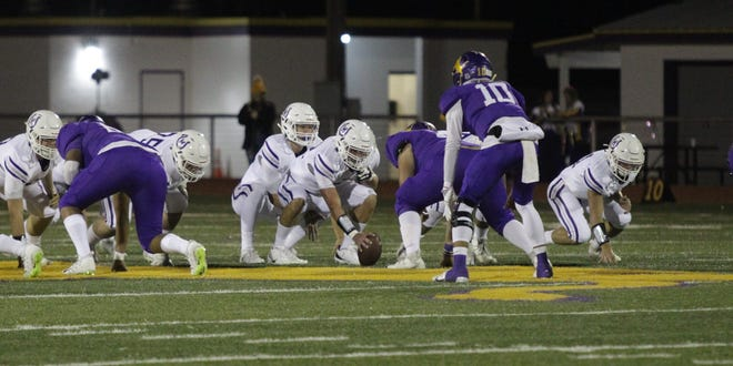 Mason High School quarterback Matthew Kerr lines up the Punchers for a play while Ozona's Jesse Vega (10) prepares to defend on Friday, Oct. 30, 2020, in Ozona in the District 14-2A Division I title game.
