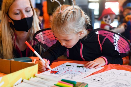 Aubrey Johnsen, 4, draws a mask on her coloring page of a dinosaur while her mom, Britni, looks on at the Washington Pavilion Halloween celebration on Saturday, October 30, in Sioux Falls.