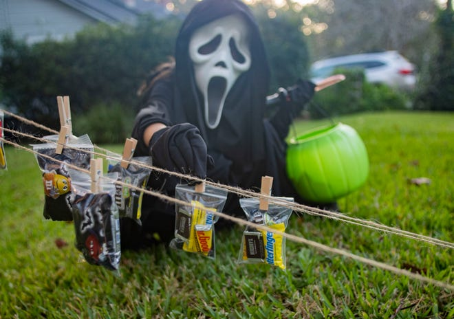 Sebastian Sadd, 8, unclips a small bag of candy from a string while trick-or-treating along Ingleside Avenue on Halloween.