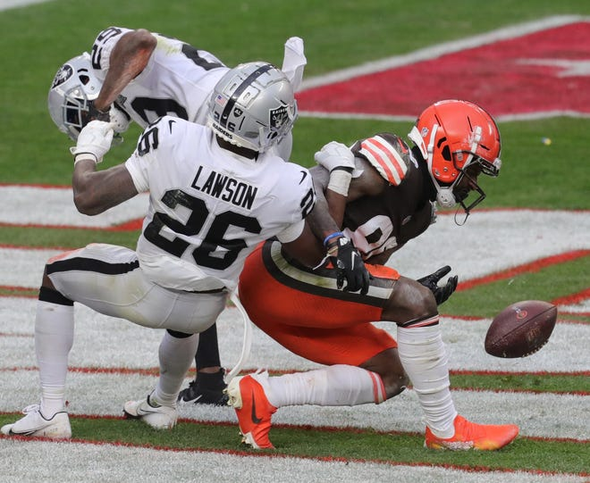 The Browns' Jarvis Landry can't get the handle on a fourth quarter pass in the end zone as Las Vegas Raiders' Lamarcus Joyner and Nevin Lawson defend on Sunday in Cleveland. The Browns lost 16-6.