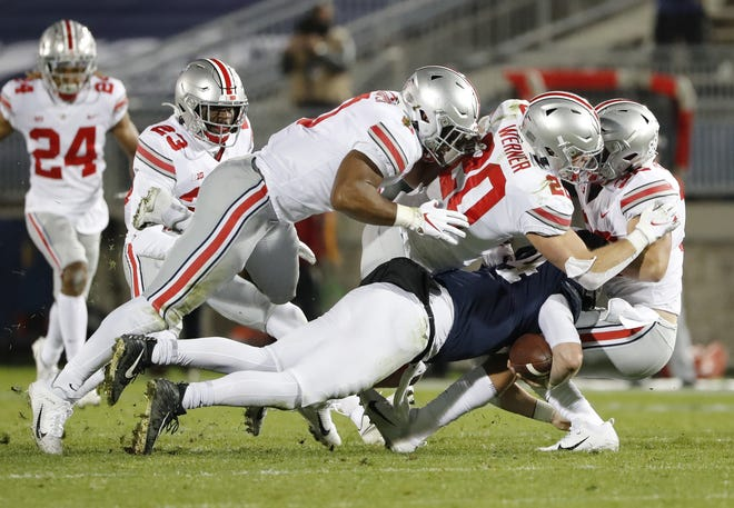 Ohio State defenders, from left, Jonathon Cooper, Pete Werner and Tuf Borland combine for a sack of Penn State quarterback Sean Clifford in the first quarter. OSU finished with five sacks and limited Penn State to 67 yards rushing.