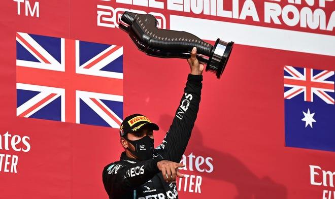 Mercedes driver Lewis Hamilton holds up the trophy after winning the Emilia Romagna Formula One Grand Prix on Sunday. [Miguel Medina, Pool via AP]