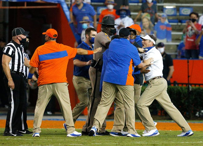 Florida head coach Dan Mullen, far right, is held back by coaches and law enforcement after a fight broke out at the end of the first half during a game against Missouri at Ben Hill Griffin Stadium in Gainesville, Fla.