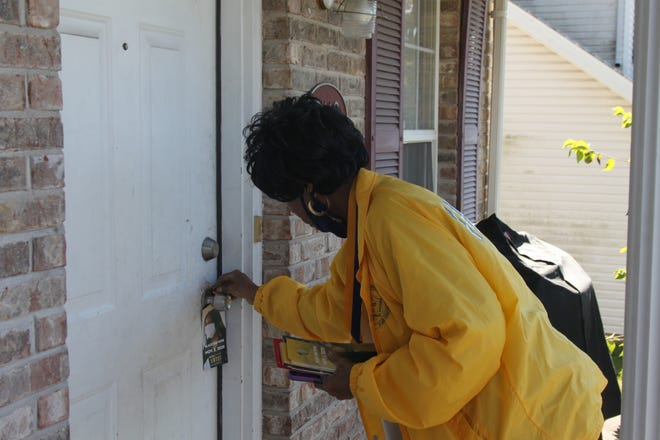 Columbia NAACP chapter president Mary Ratliff hangs a door hanger as a part of a Rock the Vote campaign on Saturday. Ratliff hopes to see the African American voter turnout increase from 59.6 in the 2016 general election.