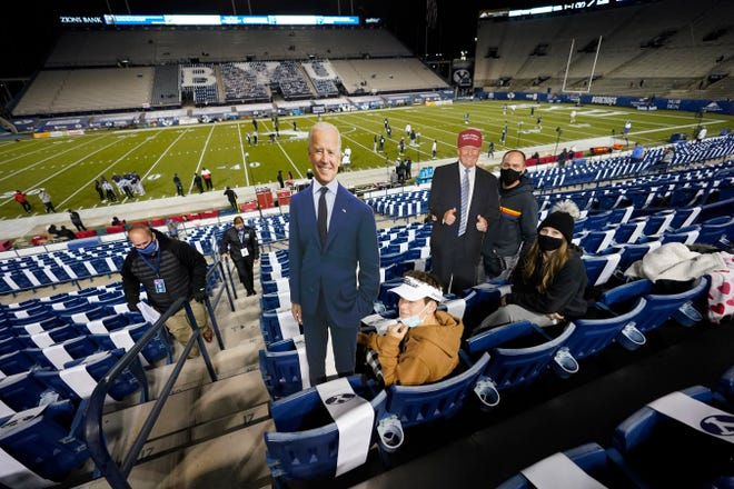BYU fans hold up cardboard cutouts of Democratic challenger Joe Biden and President Donald Trump before a football game Saturday between BYU and Western Kentucky in Provo, Utah.