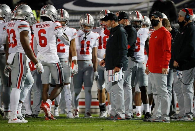 Ohio State coach Ryan Day is in self-isolation and his team is dealing with a surge in positive COVID-19 tests, putting the Buckeyes' bid for a national championship in jeopardy.