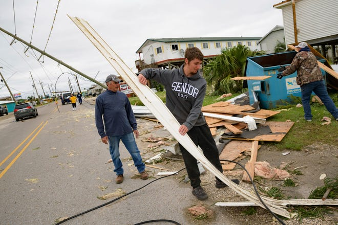 "Mark Andollina, left, and his son, Nicholas Andollina, center, remove part of a roof damaged by Hurricane Zeta at the Cajun Tide Beach Resort in Grand Isle on Friday. Gov. John Bel Edwards says the damage from Zeta was ""catastrophic"" in Grand Isle, one of the hardest-hit areas."
