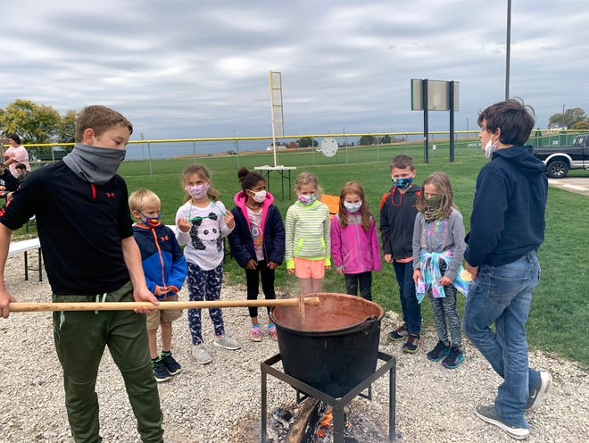 Green Elementary School students stand around the apple butter pot watching Smithville High School FFA members Jonathan Tomic (left) and Landon Clarke stir and scrape the apple butter so it doesnÕt burn.